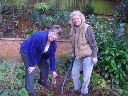 Sue Kendall, County Chairman and Gina Starling, Garden Officer, planting a Centenial Rose in the garden at WI House
